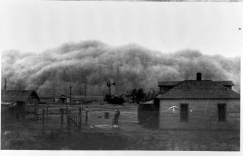 This undated photograph captures a large dust storm about to hit this family's homestead. These storms were frequent occurrences in western Kansas during the 1930s Dust Bowl.